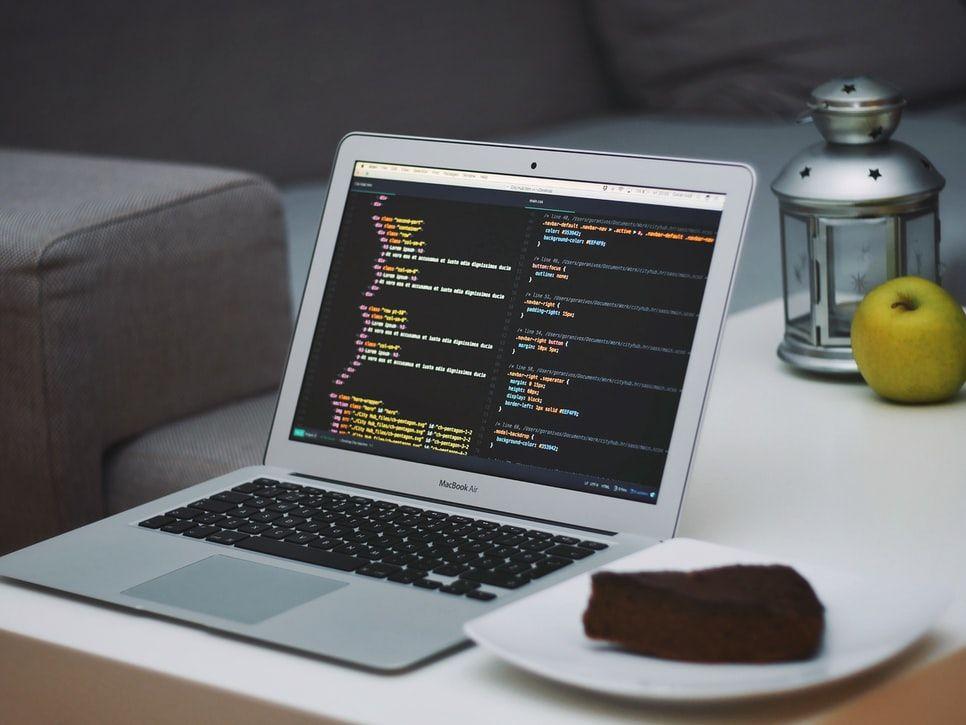 Un ordinateur ouvert sur des lignes de code et une assiette contenant une part de gâteau.
